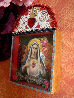 Entzückender Hausschrein mit Madonnenbildchen. Vor Rosen und verziert mit einer hübschen Spitzenborte und Blumen ein Marienbild mit flammendem Herz.De