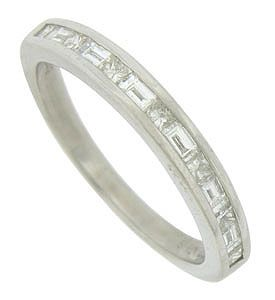 A string of round and baguette cut diamonds are channel set into the face of this smooth polished white gold wedding band. The antique style wedding ring measures 2.90 mm in width. Size 6. We can re-size.