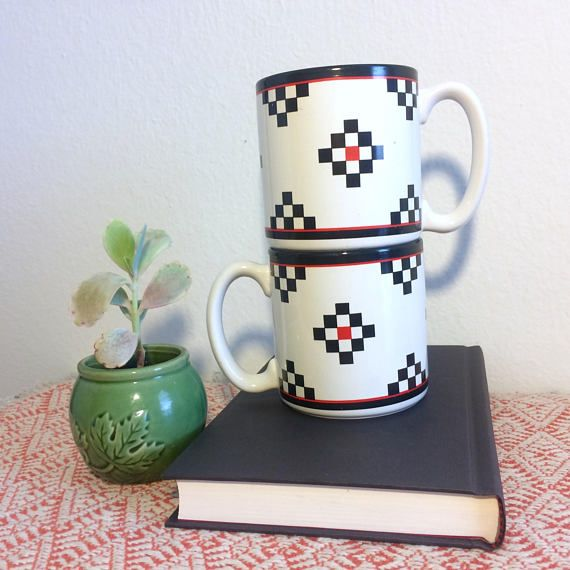 This set of 2 coffee mugs have a cool pattern that reminds us of tetris. In a sharp white background it displays red and black squares that have a vintage southwestern look. The design is unique and retro and it will look nicely in any modern trendy home! Perfect for coffee or tea for