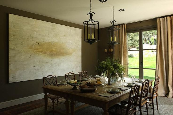 Chic brown dining room features a large abstract painting lining chocolate brown walls alongside ...