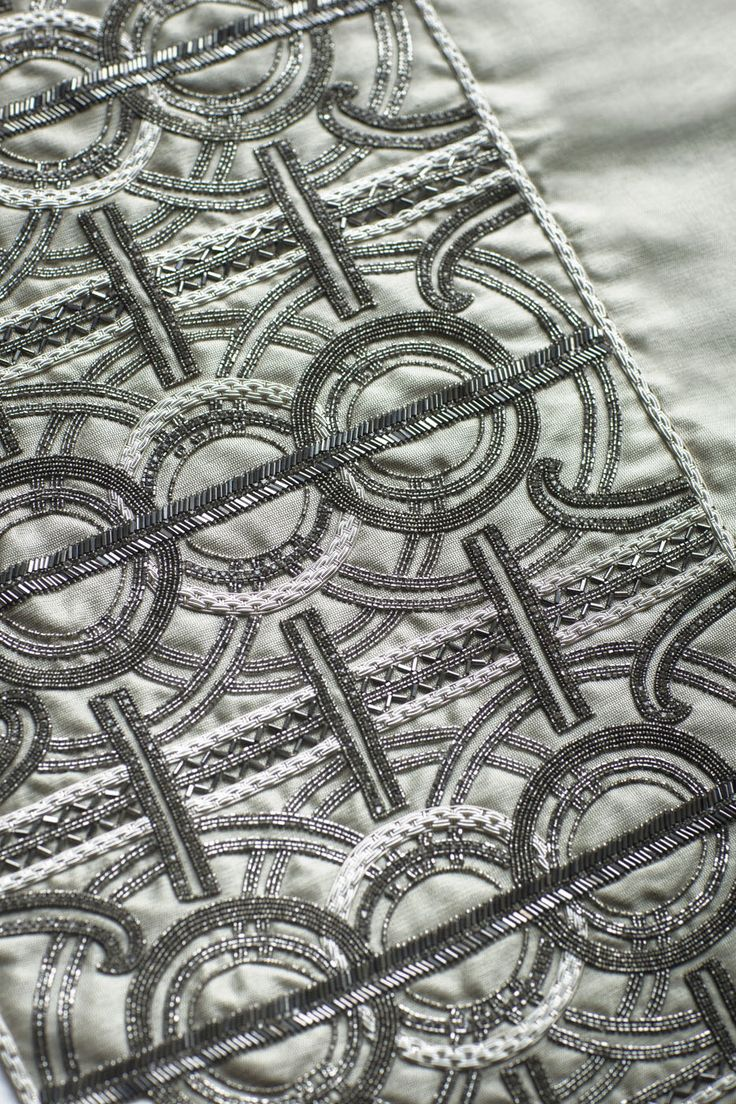 Circe is a striking couture fabric design comprising of a pattern of concentric circles and strong regimented lines. Art Deco in feel, Circe is enhanced by beautiful hand sewn beadwork that creates a design truly unique and incredibly luxurious.