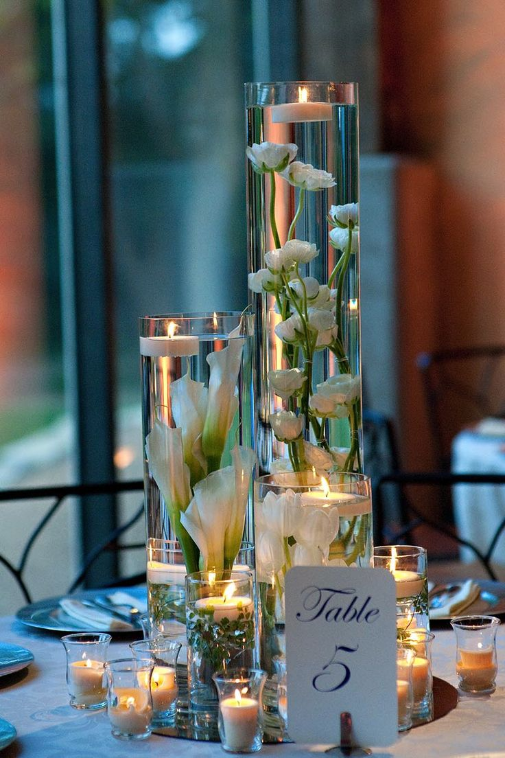 Some of the centerpieces will be a custer of tall cylinder vases with submerged orange tulips, pink peonies, and white daisies topped with floating candles and surrounded by skinny cylinders with floating candles and mercury glass votives.