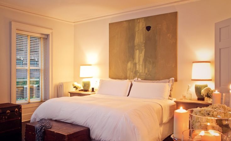 Suzie: Chango & Co. - Romantic bedroom with pale blue walls, abstract art used as headboard, ...