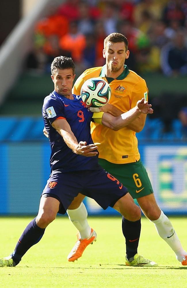 Matthew Spiranovic battles with star Dutch striker Robin van Persie