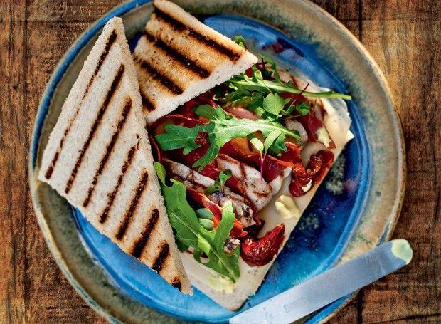 Club sandwich com frango orgânico e presunto de parma  Ingredientes 2 colheres (sopa) de maionese; 1 colher (café) de mostarda; 4 filés de peito de frango orgânico; 2 ramos de tomilho; 2 ramos de alecrim; 10 fatias de presunto de Parma; 4 rodelas de tomate seco; 120 g de queijo gruyère; 12 folhas de minirrúcula selvagem; 10 g de flor de sal de Noirmoutier; 8 fatias de pão miga; 30 g de flor de manjericão tailandês*; 30 ml de azeite extravirgem; pimenta-do-reino e sal a gosto.