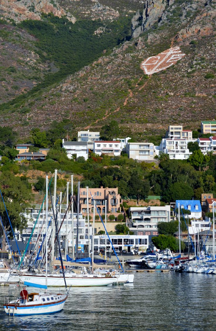 The well-known Gordons Bay sign against the Hottentots-Holland mountain behind the town. The old harbour and the yacht club is visible in the front. #GordonsBay #yachtclub