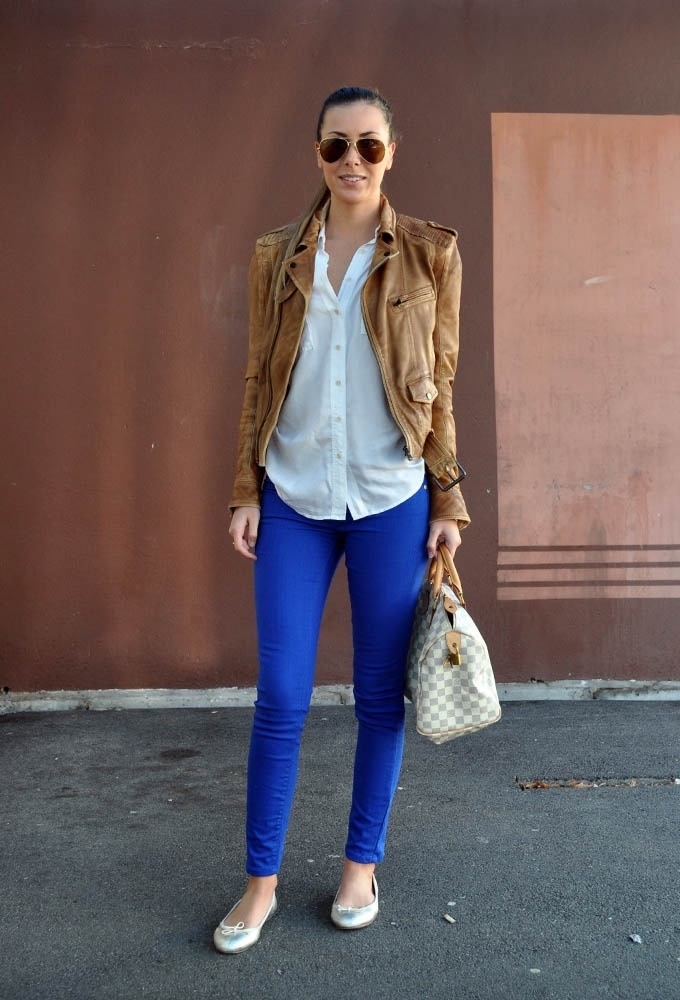 blue pants with long white top and beige leather jacket