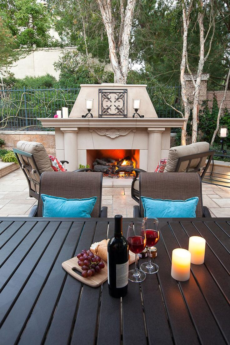 Candles, a roaring fire and pillowy rocking chairs make this Southwestern style patio feel luxurious. Wrought iron accents and decor amplify the backyard's Spanish modern vibe.