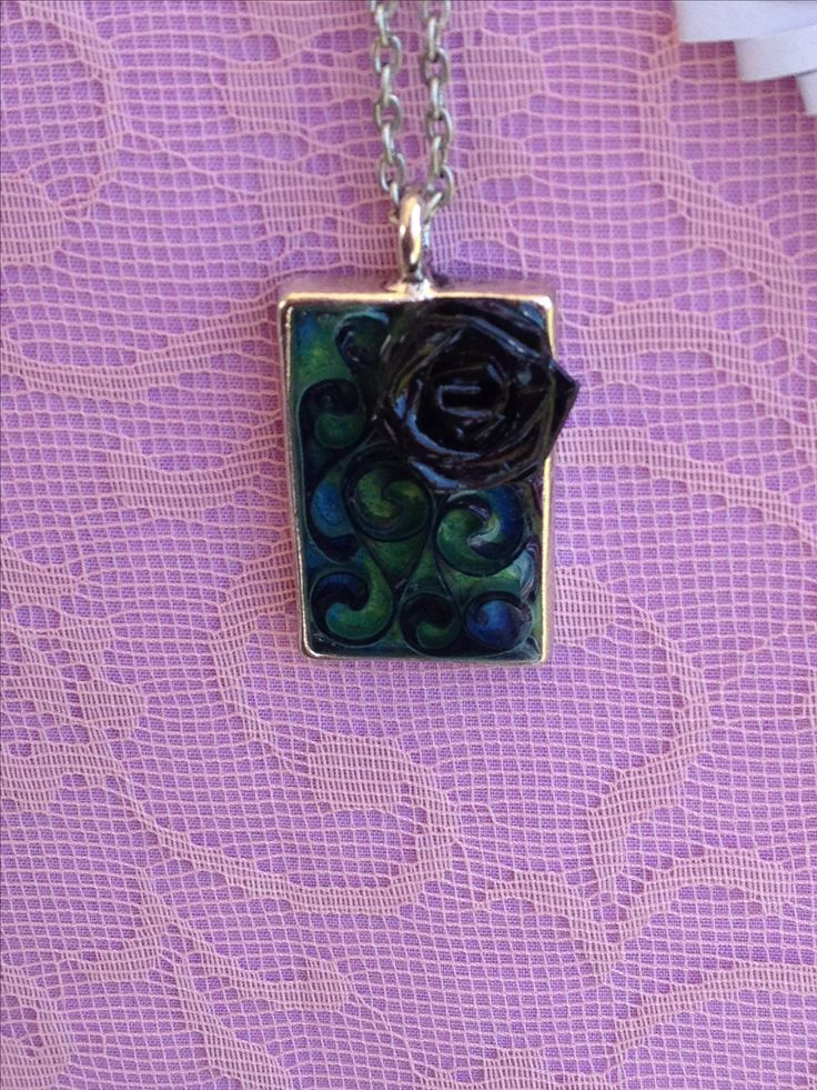 Hand folded paper rose and quilled necklace coated in resin.
