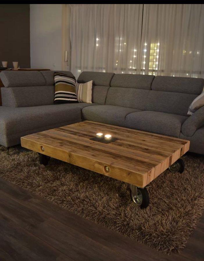 Mooie woonkamer met bruine muren, witte gordijnen, houten tafel op wielen, hoogpolig vloerkleed, bruine houten vloer en mooie grijze hoekbank.