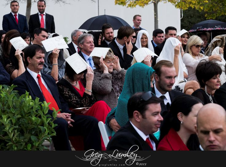 Paper umbrellas during outdoor wedding ceremony as the rain starts