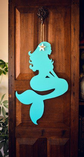 This turquoise mermaid will make any beach cottage door pop! Complete with a white starfish hair accessory, this little mermaid will welcome your guests home. Maid in our home state of NC. Dimensions: