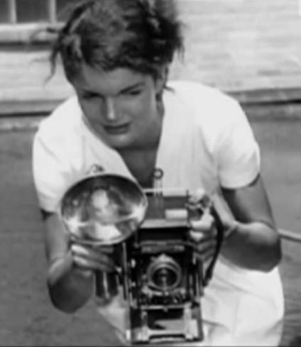 Young Jackie Bouvier Kennedy Onassis with a camera.
