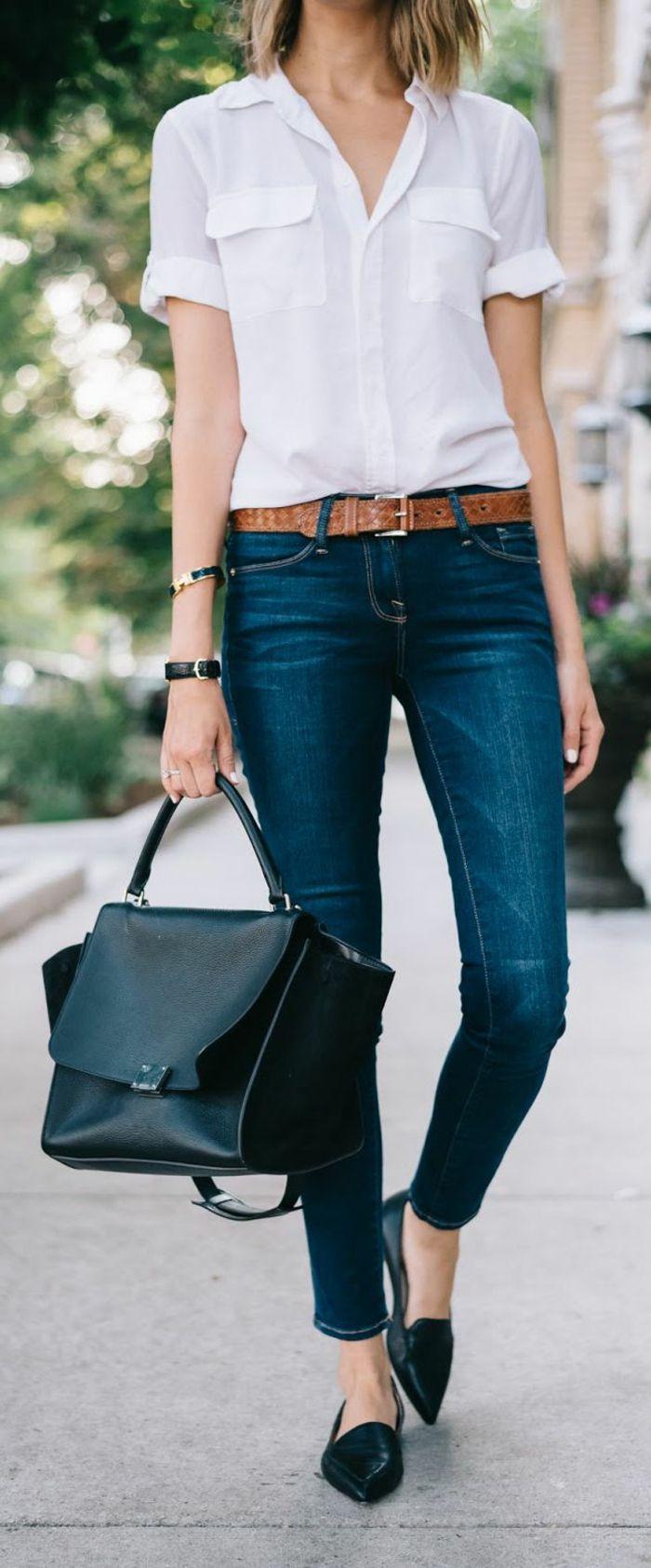 close up of a female torso, wearing white short-sleeved shirt, dark blue skinny jeans, black flats and brown belt, holding big black leather bag