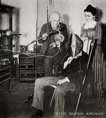 Patient Undergoing Radiation Treatment, c. 1915.   Note that both the doctor and nurse are not protected from radiation, although the patient wears a protective mask