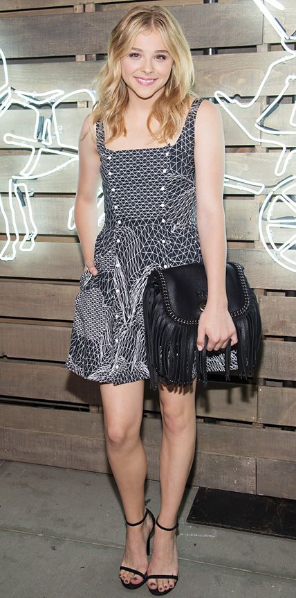 Chloe Grace Moretz arrived at the Coach 2014 Summer Party looking summer-ready in a black-and-white double-popper Christopher Kane frock, complete with Stuart Weitzman sandals and a fringe leather Coach cross-body that she turned into a clutch.