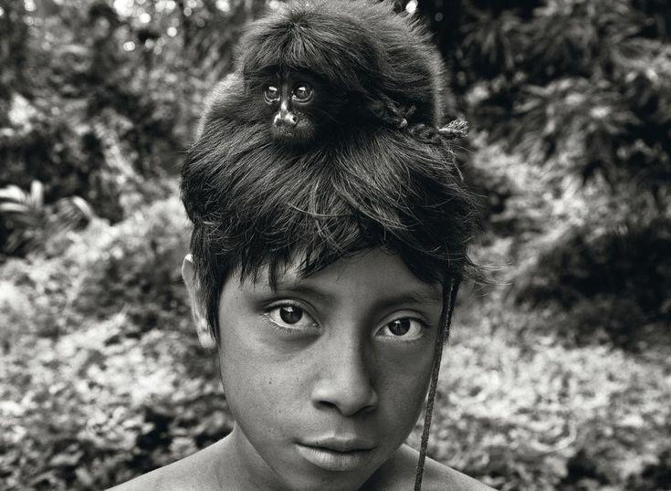 Un cachorro de mono, capturado y domesticado por los awá, yace sobre la cabeza del joven Yahara. Los awá forman una de las comunidades más amenazadas del planeta debido a la deforestación descontrolada del Amazonas brasileño. / SEBASTIÃO SALGADO (AMAZONAS IMAGES / ALBUM)
