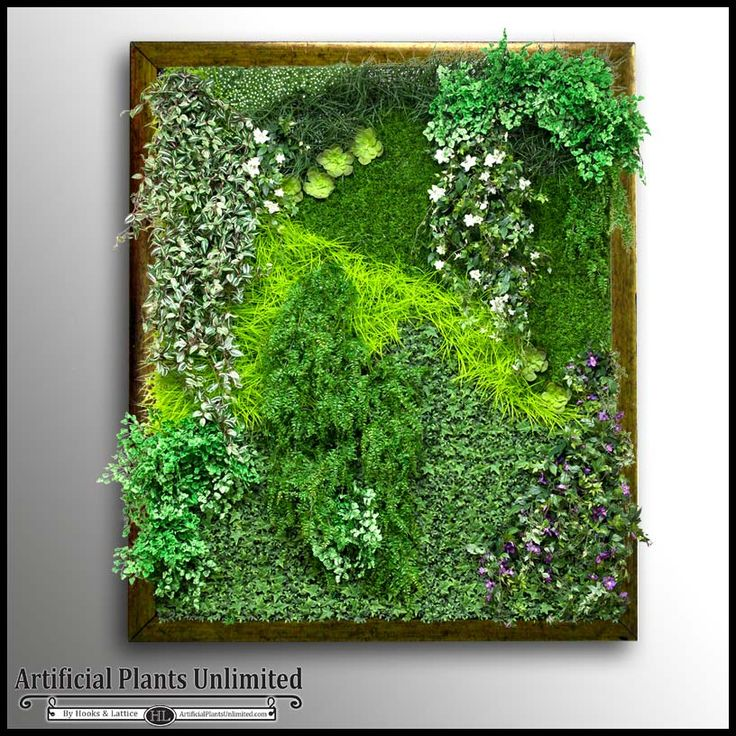 Artificial green wall with a variety of faux plants ...