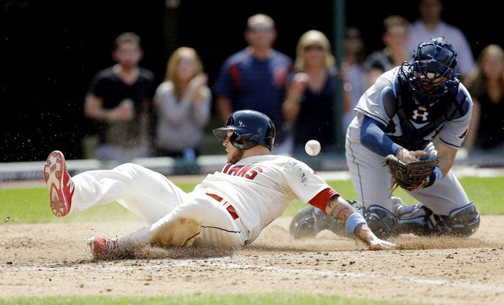 Roberto Perez slides safely into home plate as Tampa Bay Rays' Curt Casali drops the ball in the ninth inning  Sunday, June 21, 2015,