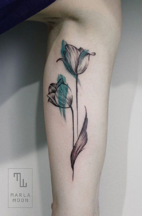 A mystical looking tulip tattoo in black and green ink.  Almost looking like a sketch, the tulip is drawn loosely with shards of green light on its petals.