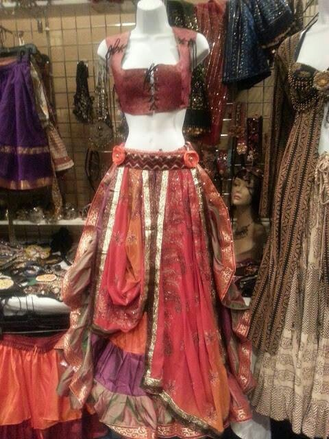 Gypsy-style leather lace-up top and fabric floor-length skirt with leather-braided belt.