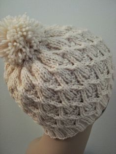 If you've always wanted to learn how to knit a hat, with this free knitting pattern for a Wickerwork Hat. Complete with an adorable yarn pom pom, this easy knit hat pattern is perfect for young and old alike. #Knit #Pattern #Free