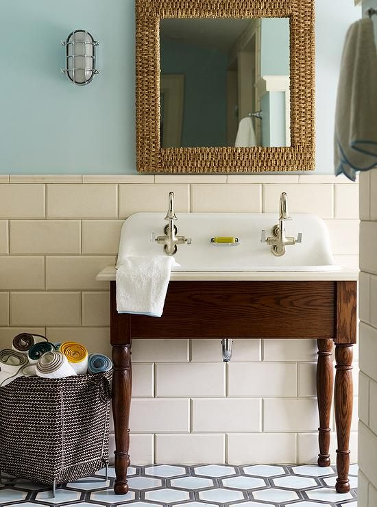 Blue cottage bathroom features upper walls painted sea blue and lower walls clad in large cream tiles lined with an oak sink vanity with turned legs fitted with a trough sink and two vintage gooseneck faucets as well as a square woven mirror lit by nautical cage sconces.
