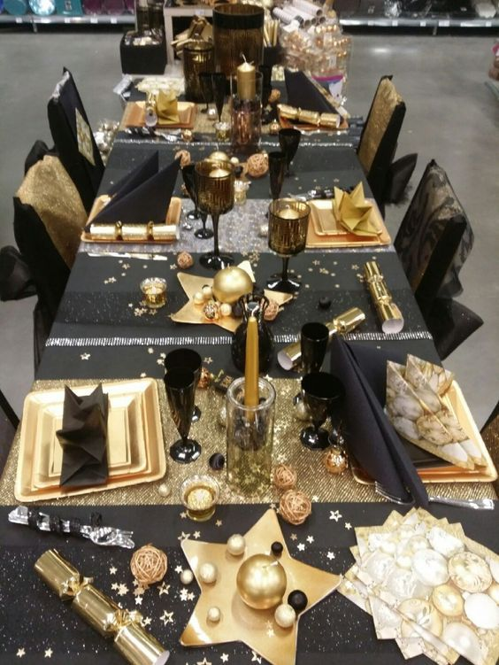a black and shiny metallic tablescape with lots of ornaments, stars, metallic chargers looks very bold and glam