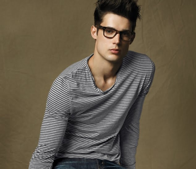 Long sleeves gray v-neck. Black glasses. Brown hair.
