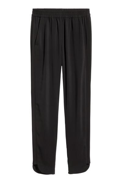 Wide, high-waisted trousers in a crêpe weave with an elasticated waist, side pockets, a welt back pocket and tapered legs with piping down the sides and a s