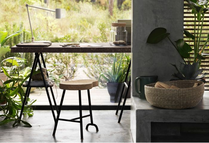 A sunny living room with a desk in dark brown cork and black powder coated steel. Combined with a stool in natural cork with black legs.