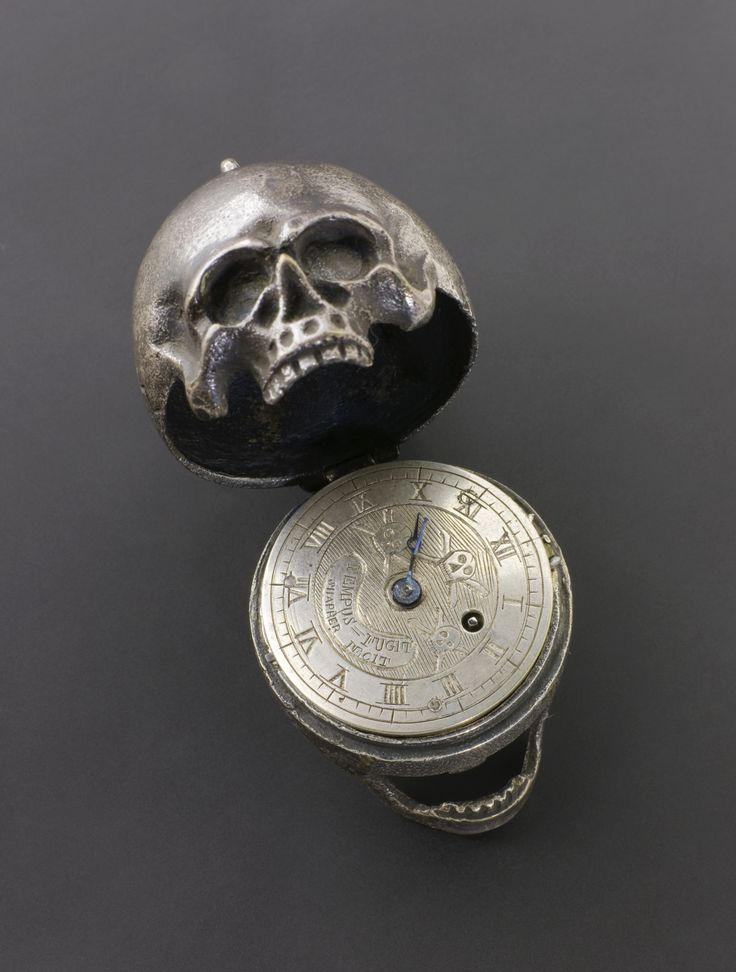 Memento Mori Rubin Museum 2013.  Skull Pocket Watch, Europe; 1701-1900; Silver model of a human skull which opens up to show a pocket watch inside inscribed with skull and cross bone; Silver; Science Museum, London
