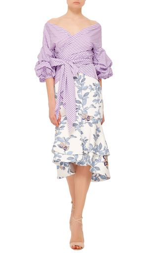 Rendered in cotton sateen with a floral design, this **Johanna Ortiz** skirt features a high rise waist, a formfitting silhouette, and a fluted midi length hem with dual ruffle layers.