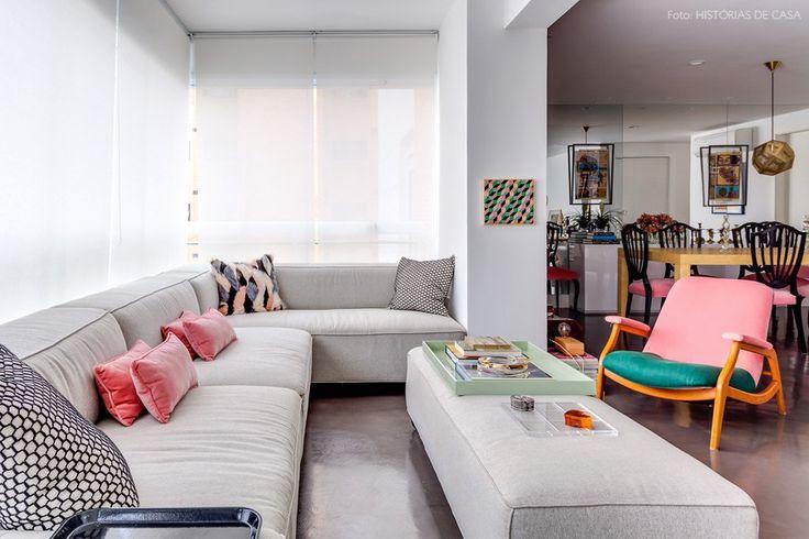 Varanda integrada com a sala de estar. O sofá cinza em L acomoda as visitas e as almofadas em tons de rosa, escolhidas pela moradora