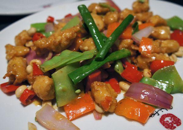 Chicharon de Frango Bruce Lee: pedaços macios de frango empanados levemente e fritos, então salteados em wok com pimentas peruanas e dedo de moça, amendoim, legumes e molho a base de ají rocoto