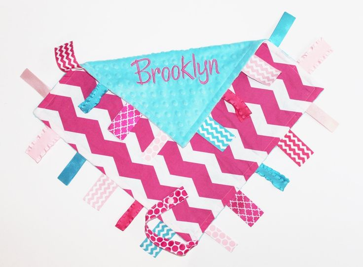 """Personalized Chevron Ribbon Tag Blanket with Pacifier Clip, Hot Pink and Turquoise Minky, Sensory Blanket, 16""""x16"""". Ribbon tag blanket with pacifier clip leash and personalized with baby's name. Made with the Hot Pink and White Chevron cotton fabric and backed with a Turquoise dot minky. Ribbon tags in Hot Pink, Light Pink and Turquoise. Blanket measure approx 16"""" x 16"""" not including ribbons. Ribbon loops have been cut and heated sealed. Also attached is a pacifier leash with a snap."""