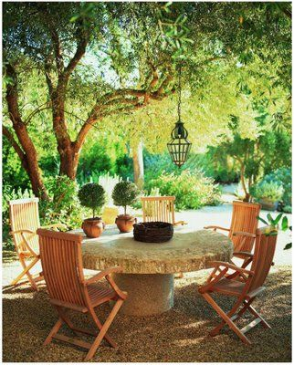 Interior Designer and Home of John Saladino's Shaded Secret Garden and features a table made from a 900-year-old Chinese gristmill stone placed on a pedestal.