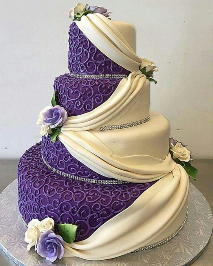 What a gorgeous cake. Dark purple with scrolling detail and cream colored draped fondant. The silver beading and airbrushed flowers bring it all together.