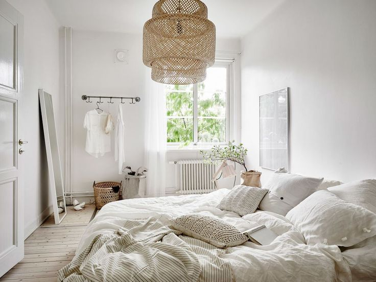 Bedroom: white bed linen, scatter cushions, pale wicker/straw pendant light, full-length mirror with white frame, pale limewashed floorboards, wall-mounted clothes rack, wicker basket, plant