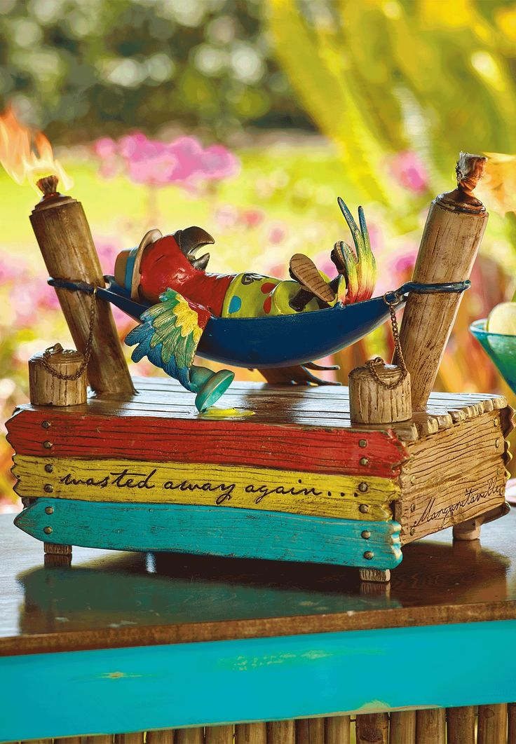 We still aren't sure if this colorful parrot is passed-out or simply napping the day away. Regardless, this aluminum tabletop torch features two torches cleverly disguised as dock posts. | Margaritaville by Frontgate
