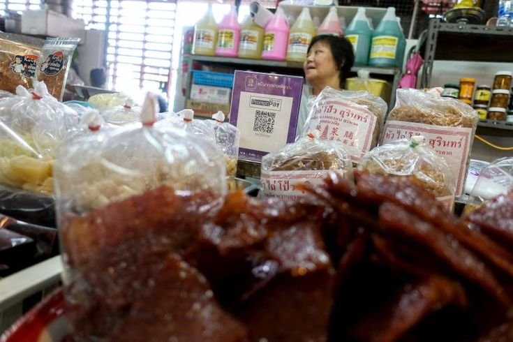 BANGKOK (Reuters) – Bangkok's famous street-food vendors have joined the digital revolution, embracing payment via Quick Response (QR) barcodes that can be read using smartphones.    An advertisement board displaying a QR code is seen as a vendor waits for customers at a market in B...