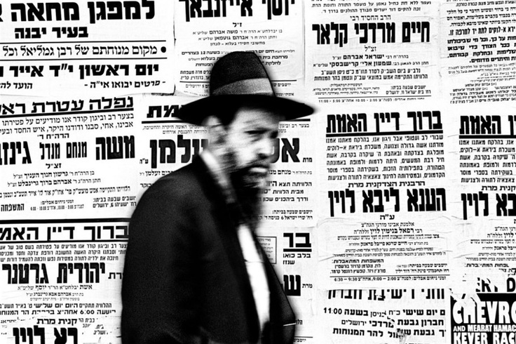 An ultra-Orthodox Jewish man walks past a wall of pashkevilim in a Haredi neighborhood in Jerusalem. These traditional posted announcements are a popular means of communication in the Orthodox community.