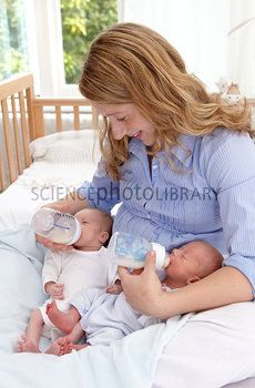 twin bottle feeding | Mother feeding two week old twins - Stock Image F007/0016 - Science ...