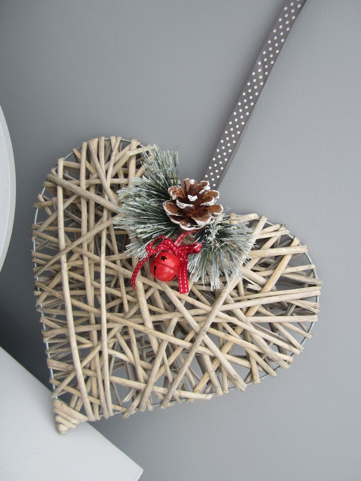 Natural Wicker in a beautiful large heart shape. Perfect for a festive front door. The top of the heart has fir branches, a pine cone and a jingly bell.