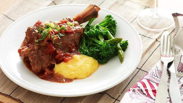 Lamb shanks are cooked for over six hours in a slow cooker to produce this incredibly rich and delicious lamb dish. Served with instant polenta and crisp greens