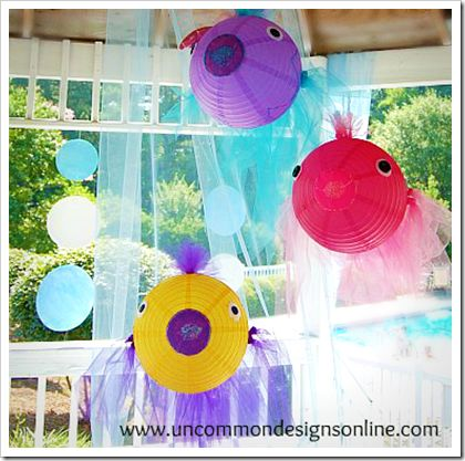 Fish lanterns at a mermaid pool party. Also check out her great tulle and appliqued tablecloth.
