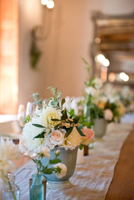 Rustic cream, blush and peach wedding. Olive and herb greenery with rose, stocks, dahlias and spray roses in loose, organic arrangements using duck egg urns and vintage bottles for centrepieces.