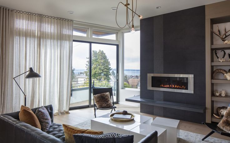 """The living room was the first to come together,"" says interior designer Joy Rondello<br/> of J+Studio, who met Magnolia homeowners Katie Finch and Steven Rinella through Homepolish. The modular cubes of the CB2 coffee table double as extra seating; ""It's especially cool they fit under the fireplace,"" says Rinella. The modern-industrial brass chandelier by Workstead ""is kind of fun but not too precious,"" says Rondello.  (Steve Ringman/The Seattle Times)"