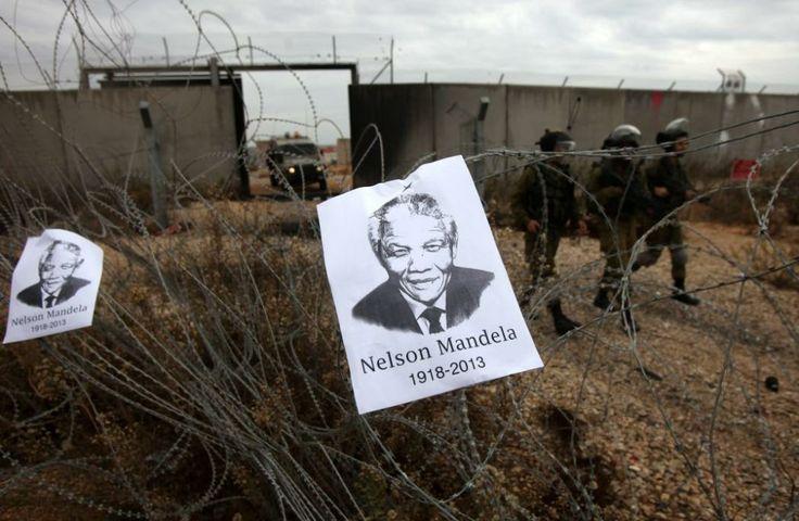 Retrato del ex presidente sudafricano Nelson Mandela cuelga del alambre de púas mientras soldados israelíes tratan de dispersar a manifestantes palestinos en la villa de Bilin (Cisjordania). (AFP/ABBAS MOMANI/VANGUARDIA LIBERAL)