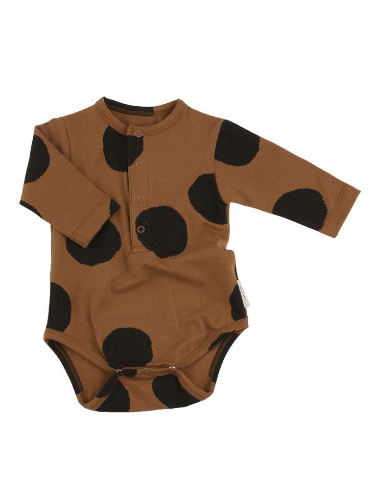 Fin långärmad body från Tiny Cottons. Bodyn är brunt med svarta prickar. Bodyn har tryckknappar i nacken samt i grene för enklare av- och påklädning. Matchar fint med bruna leggings från Tiny Cottons.